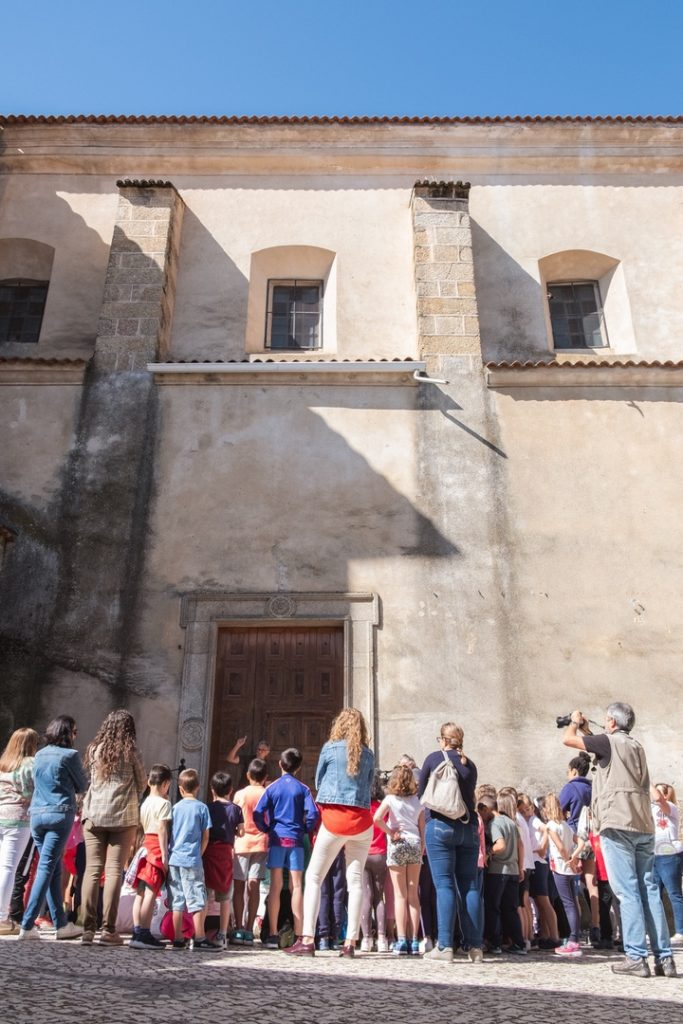 Vista De la Iglesia de San Vicente de Alcántara con un grupo de escolares a las puertas durante una actividad de educación ambiental